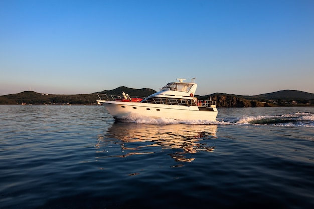Motorboot, das sich bei sonnenuntergang im meer bewegt