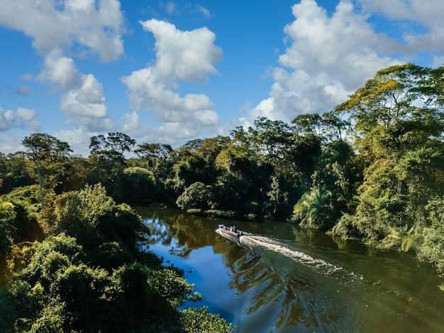 Motorboot im see, umgeben von schönen grünen bäumen unter einem bewölkten himmel