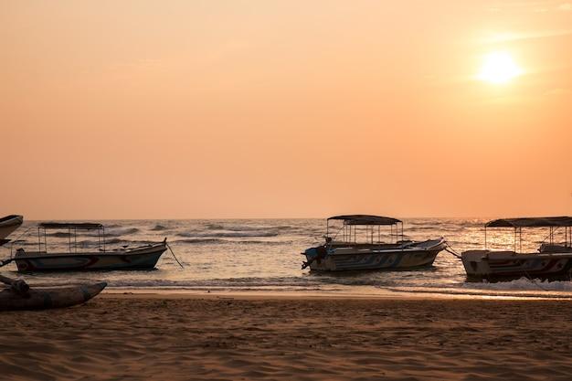 Motorboote an der ozeanküste bei sonnenuntergang, sri lanka