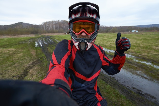Motorcross-fahrer posiert für selfie, während er den daumen gegen die natürliche umgebung zeigt