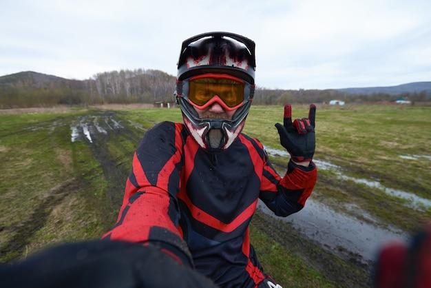 Motorcross-fahrer posiert für selfie, während er sich vor der kamera bewegt