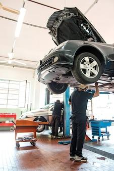 Motormechaniker, der an einem auto an einem hebezeug arbeitet