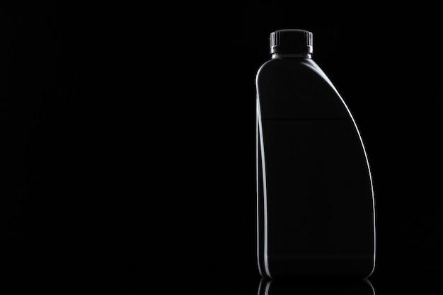 Motorölflasche auf schwarzem hintergrund, nahaufnahme.
