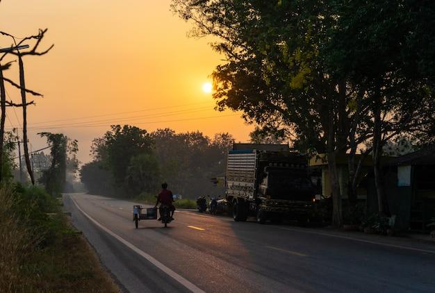 Motorrad auf asphaltstraße am landschafts- und sonnenscheinmorgen