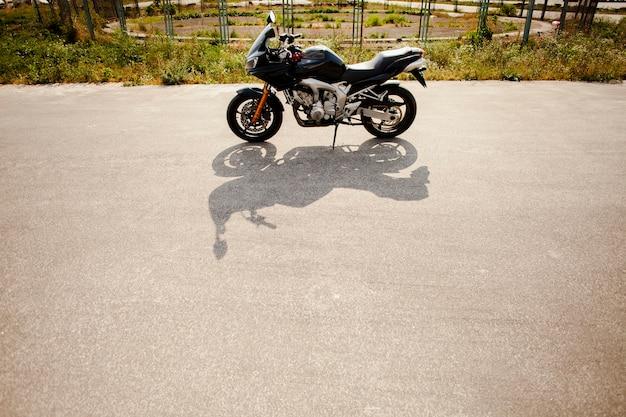 Motorrad auf der straße mit seinem schatten