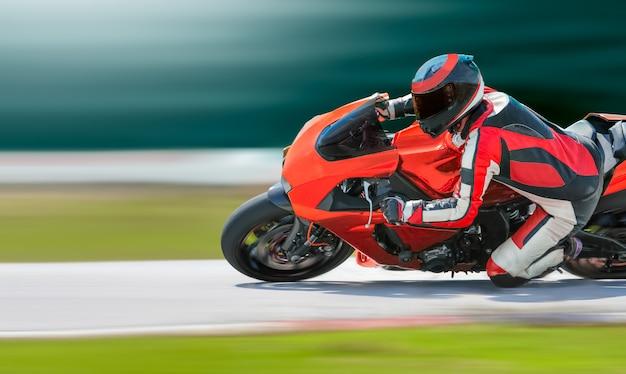 Motorrad, das in eine schnelle ecke auf rennstrecke sich lehnt