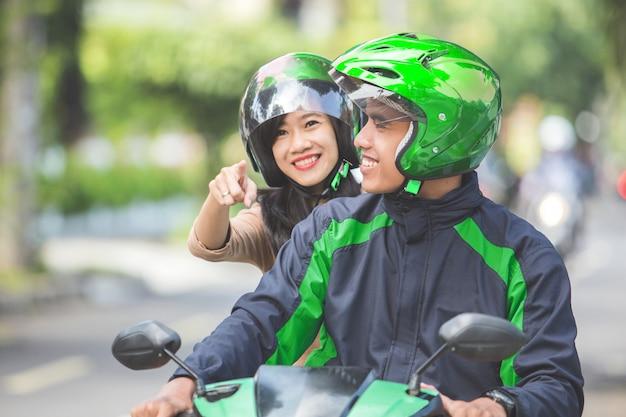Motorrad-taxifahrer bringt seinen passagier zu ihrem ziel
