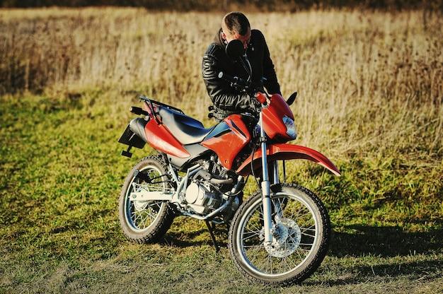 Motorradfahrer bleiben bei sonnenuntergang mit ihm fahrrad
