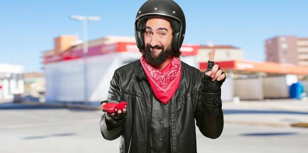 Motorradfahrer, der ein rotes automodell hält