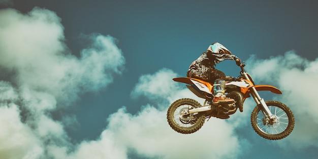 Motorradfahrer fliegen am blauen himmel. extremes konzept, weitsprung auf einem motorrad.