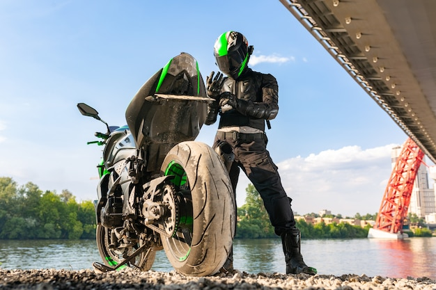 Motorradfahrer in helm und schutzanzug steht unter der brücke