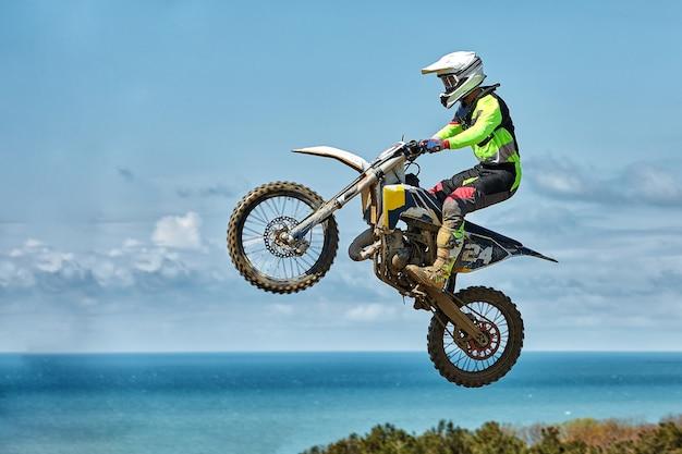 Motorradfahrer macht einen extremen sprung gegen den himmel