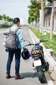 Motorradfahrer steht an seinem fahrrad, nimmt den helm auf und macht sich fahrbereit