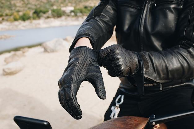 Motorradfahrer trägt lederhandschuhe