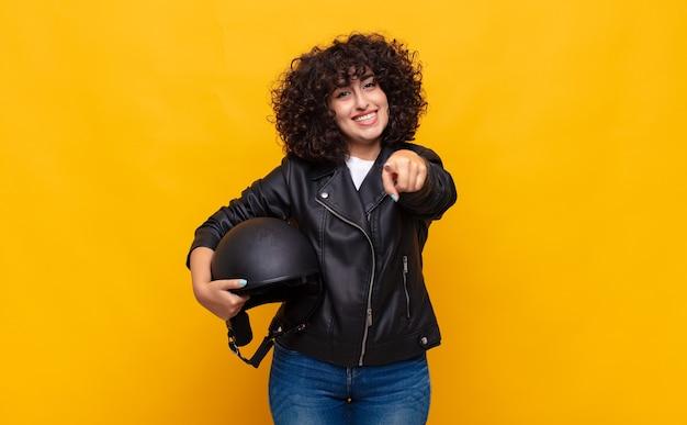 Motorradfahrerfrau, die mit einem zufriedenen, selbstbewussten, freundlichen lächeln auf kamera zeigt und sie wählt