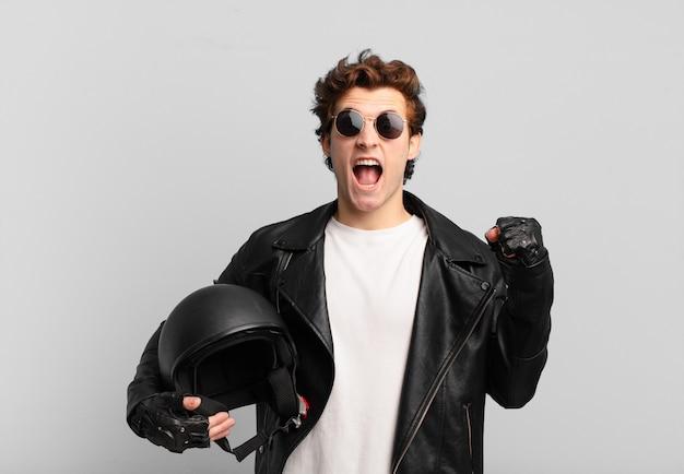 Motorradfahrerjunge, der aggressiv mit einem wütenden ausdruck oder mit geballten fäusten schreit, um den erfolg zu feiern