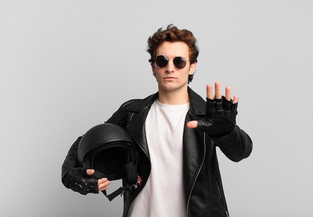 Motorradfahrerjunge, der ernst, streng, unzufrieden und wütend aussieht und offene handfläche zeigt, die eine stoppgeste macht
