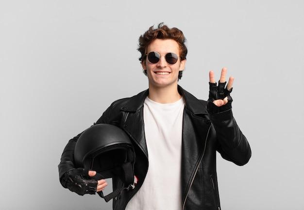 Motorradfahrerjunge, der lächelt und freundlich aussieht, nummer drei oder dritte mit der hand nach vorne zeigt, herunterzählt