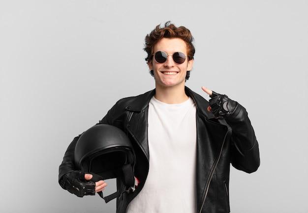 Motorradfahrerjunge, der selbstbewusst auf sein eigenes breites lächeln lächelt, positive, entspannte, zufriedene haltung