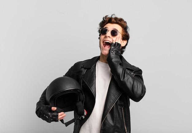 Motorradfahrerjunge, der sich glücklich, aufgeregt und überrascht fühlt und mit beiden händen im gesicht zur seite schaut