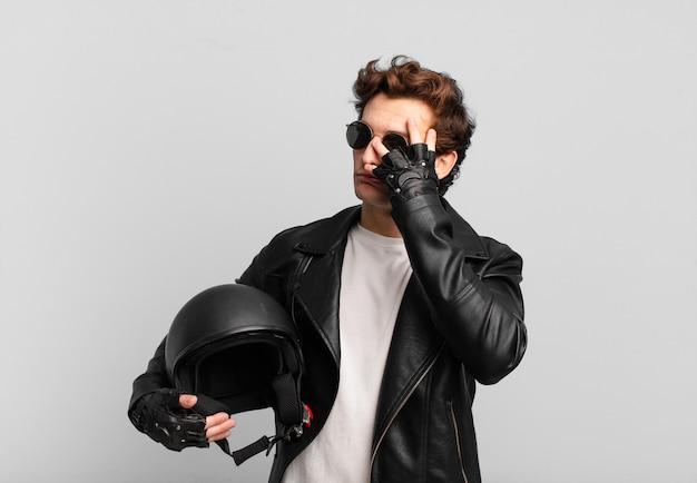 Motorradfahrerjunge, der sich nach einer ermüdenden, langweiligen und mühsamen aufgabe gelangweilt, frustriert und schläfrig fühlt und das gesicht mit der hand hält