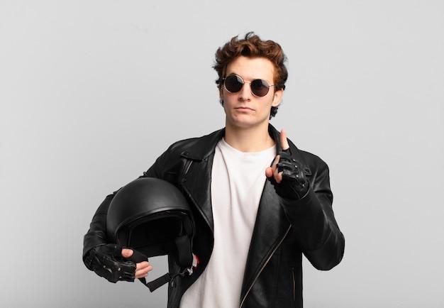 Motorradfahrerjunge, der sich wütend, verärgert, rebellisch und aggressiv fühlt, den mittelfinger dreht und sich wehrt