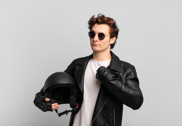 Motorradfahrerjunge sieht arrogant, erfolgreich, positiv und stolz aus und zeigt auf sich selbst