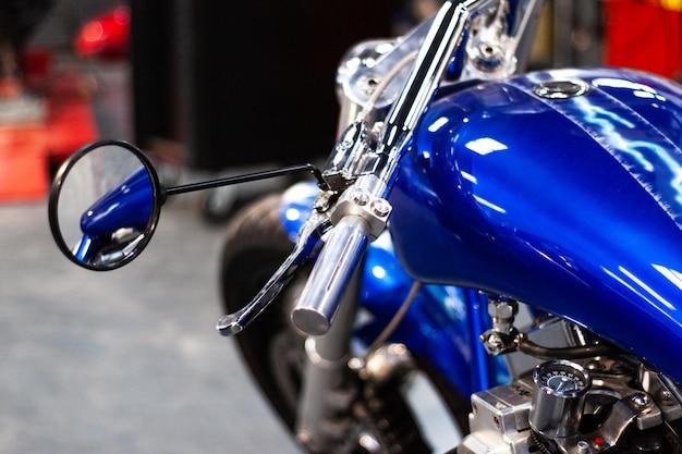 Motorradlenker und rückspiegel. chrom glänzend sauberer motorradlenker in einer mechanischen werkstatt. nahaufnahme