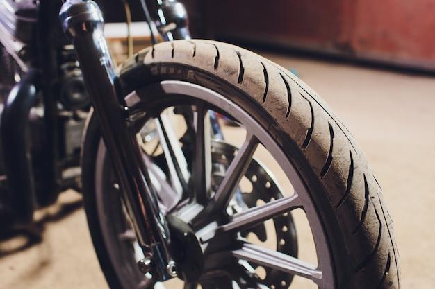 Motorräder auf dem boden mit werkstattwerkzeugen, einer modernen garage, lagerung und reparatur. dieses fahrrad wird perfekt sein. reparatur eines motorrades in einer werkstatt.