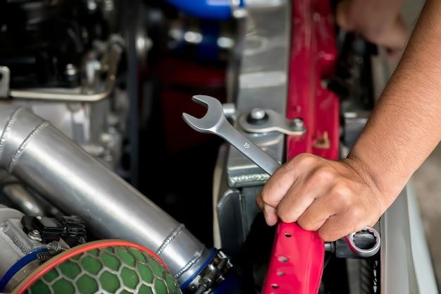 Motorreparaturtechniker halten den schlüssel, um das auto zu reparieren.