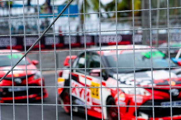 Motorsport-autorennen auf asphaltstraße. ansicht von der zaunmaschenfiletarbeit auf unscharfem auto auf rennbahnhintergrund.
