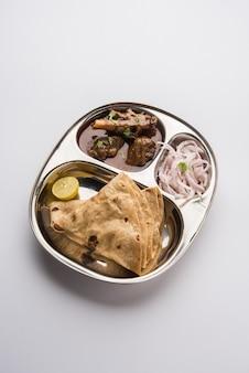 Motton thali or gosht, lammplatte ist ein indisch-asiatisches, nicht vegetarisches mittags- oder abendmenü bestehend aus fleisch, eiercurry mit chapati, reis, salat und süßem gulab jamun