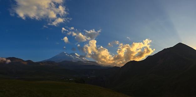 Mount elbrus während des sonnenuntergangs in den sonnenstrahlen