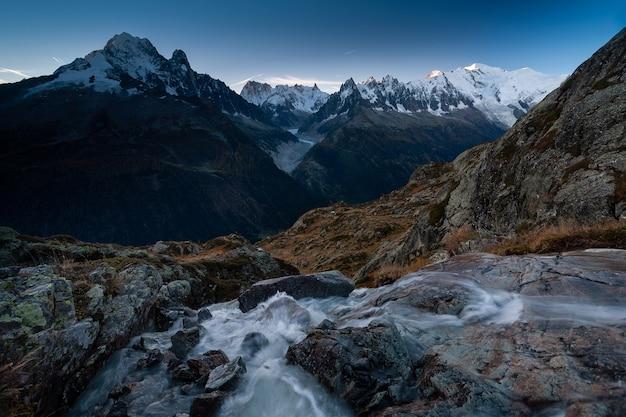 Mount mont blanc, umgeben von felsen und einem fluss mit langer exposition in chamonix, frankreich