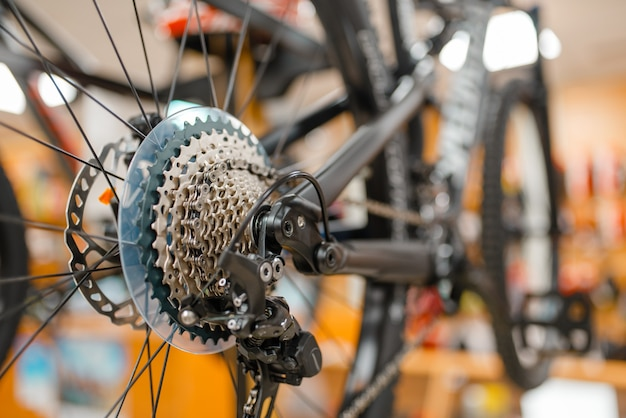Mountainbike, hinterrad mit gangschaltung, sportgeschäft, niemand, fokus auf schalthebel. sommer aktive freizeit, schaufenster mit fahrrädern, fahrradverkauf, professionelle ausrüstung für extremes fahren