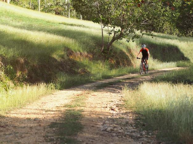 Mountainbiker des männlichen athleten fährt fahrrad entlang einer landschaftsspur. morgen sonnig.