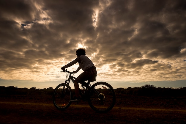 Mountainbiker-frau in aktion mit goldenem, wunderschönem sonnenuntergang, silhouette des athleten, der auf dem fahrrad der straße folgt und die sommerzeit genießt
