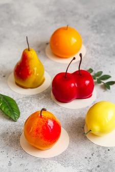 Mousse-dessert in form einer birnenfrucht, orangenfrucht, aprikose, zitrone und kirsche.