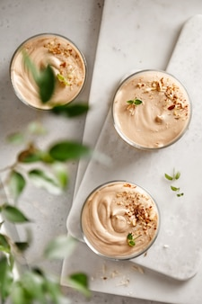 Mousse dessert mit schokoladenpaste käse und sahne mit nüssen auf dem tisch und auf dem brett