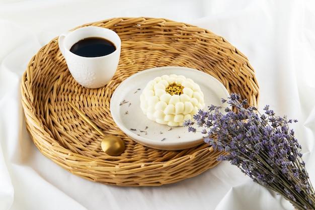Mousse-kuchen mit einer tasse kaffee und einem strauß lavendel auf einem tablett