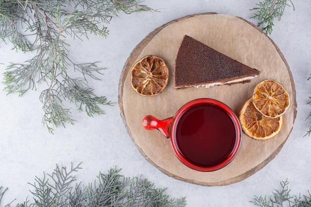 Mousse-kuchen, orangenscheiben und tasse tee auf holzstück. foto in hoher qualität