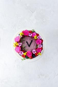 Moussekuchen mit blumen in form einer uhr verziert. vertikale ausrichtung, draufsicht, flache lage.