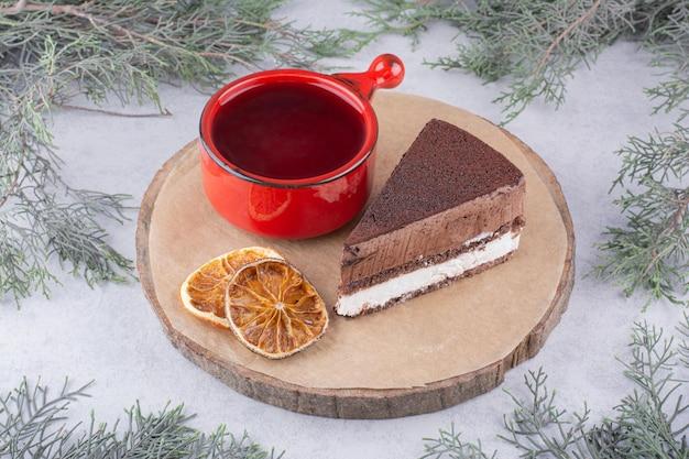 Moussekuchen, orangenscheiben und eine tasse tee auf holzstück.