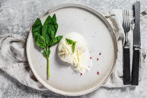 Mozzarella burrata-käse auf einer weißen platte mit basilikumblättern. grauer hintergrund. ansicht von oben