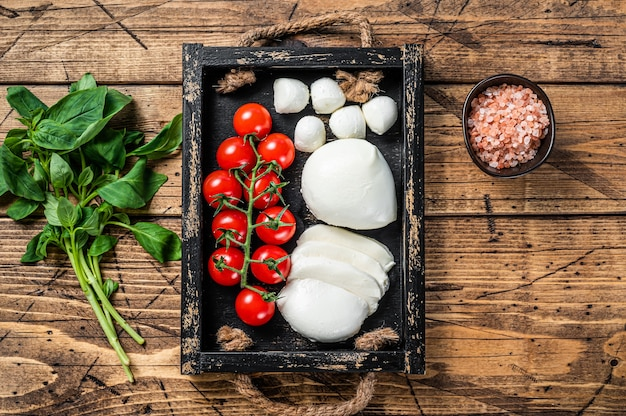 Mozzarella-käse, basilikum und tomatenkirsche in holztablett, caprese-salat. hölzerner hintergrund. draufsicht.