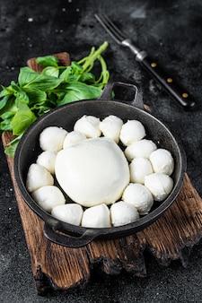 Mozzarella-käse-minibällchen in der pfanne mit basilikum. schwarzer hintergrund. draufsicht.