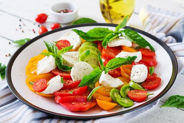 Mozzarella-käse, tomaten und basilikum-kräuterblätter im teller auf dem weißen holztisch. capresesalat. italienisches essen.