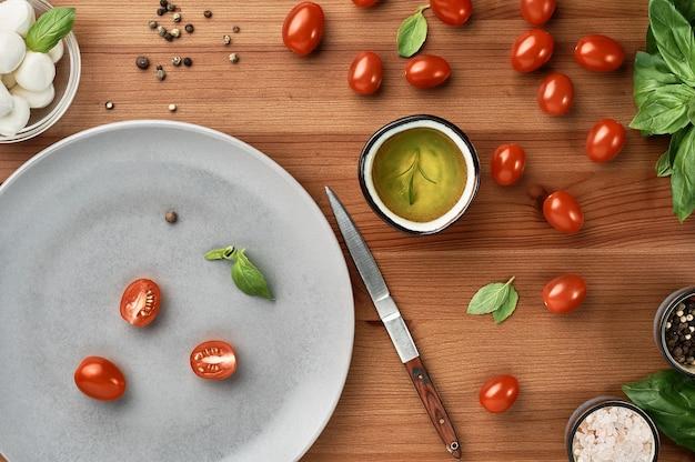 Mozzarella und kirschtomaten mit basilikumblättern, salz und pfeffer, layout auf einem holzbrett. der prozess der zubereitung von italienischem caprese-salat. draufsicht