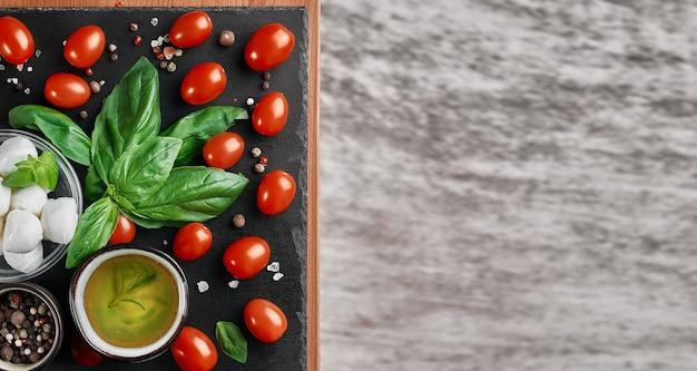 Mozzarella und kirschtomaten mit basilikumblättern, salz und pfeffer, layout auf einem schwarzen steinbrett. zutaten für die herstellung von caprese-salat. draufsicht mit kopierraum für text