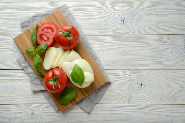 Mozzarella und tomate mit basilikumblättern auf einem weißen hölzernen hintergrund